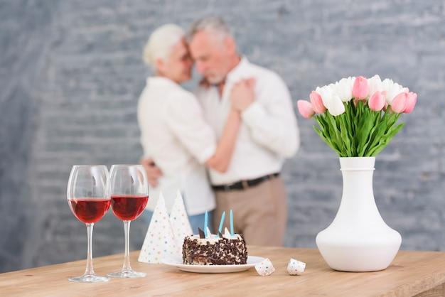 Bicchiere di vino; cappello da festa; torta di compleanno e vaso di fiori sul tavolo davanti ballare coppia offuscata Foto Gratuite
