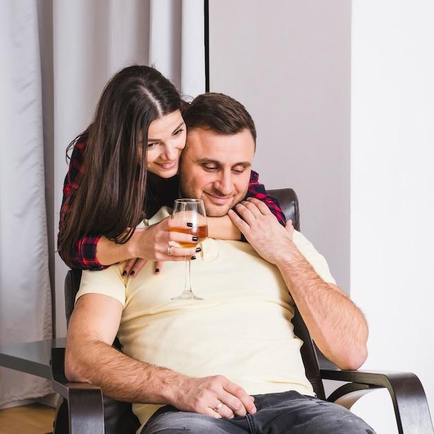 Bicchiere di vino della holding della giovane donna a disposizione che abbraccia il suo ragazzo che si siede sulla poltrona Foto Gratuite