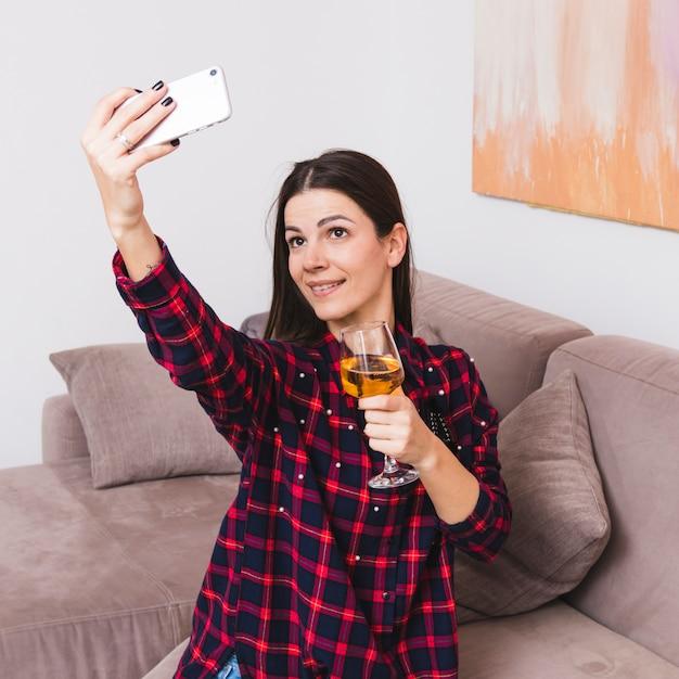 Bicchiere di vino della holding della giovane donna a disposizione prendendo selfie sul telefono cellulare Foto Gratuite