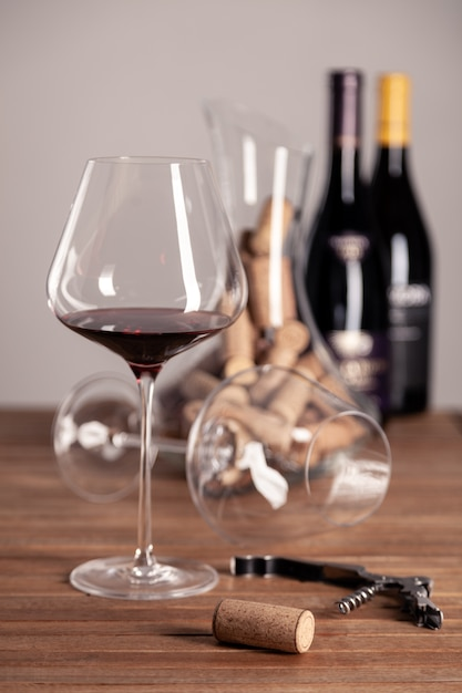 Bicchiere di vino rosso, bottiglie, cavatappi, decanter, tappi su tavola di legno Foto Premium