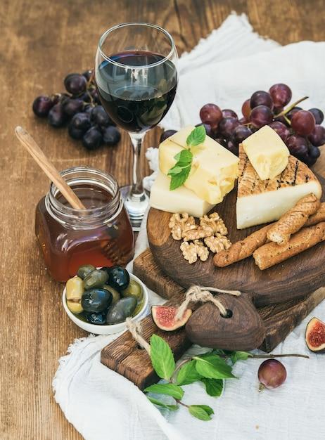 Bicchiere di vino rosso, tagliere di formaggi, uva, fichi, fragole, miele e grissini sul tavolo di legno rustico Foto Premium