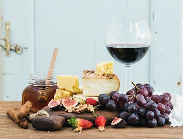 Bicchiere di vino rosso, tagliere di formaggi, uva, fichi, fragole, miele e grissini sulla tavola di legno rustica, blu Foto Premium