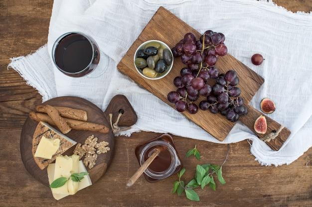 Bicchiere di vino rosso, tagliere di formaggi, uva, noci, olive, miele e grissini sul tavolo di legno rustico Foto Premium