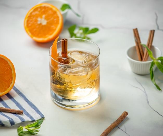 Bicchiere di whisky con cannella sul tavolo Foto Gratuite
