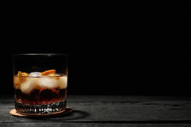 Bicchiere di whisky con cubetti di ghiaccio su fondo di legno scuro, spazio per il testo Foto Premium
