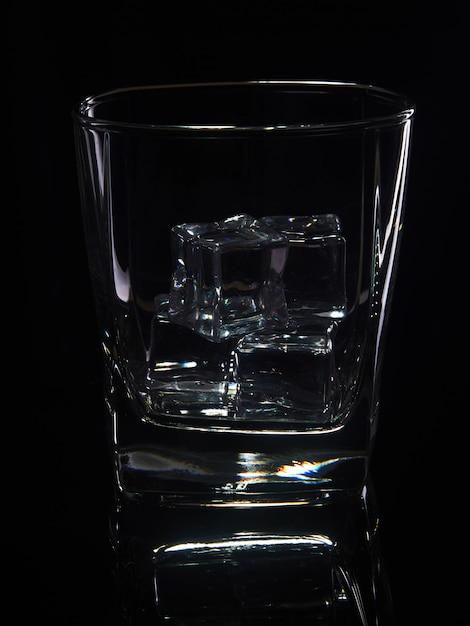 Bicchiere di whisky con ghiaccio su uno sfondo nero con la riflessione Foto Premium