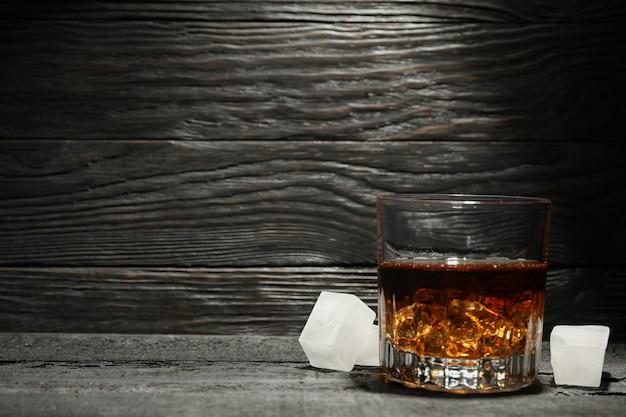 Bicchiere di whisky e cubetti di ghiaccio su fondo di legno scuro, spazio per il testo Foto Premium