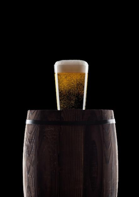 Bicchiere freddo di birra artigianale sul vecchio barilotto di legno su sfondo nero con rugiada e bolle Foto Premium