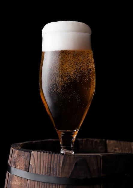 Bicchiere freddo di birra artigianale sul vecchio barilotto di legno su sfondo nero Foto Premium