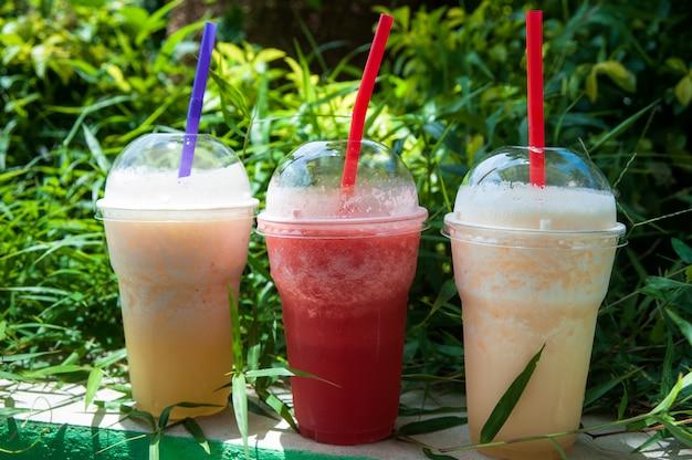 Bicchieri con frullati di ananas, mango e anguria. bevande analcoliche, nutrizione Foto Premium