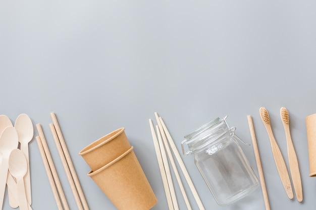 Bicchieri di carta eco naturale, cannucce, posate in legno distese su grigio Foto Premium