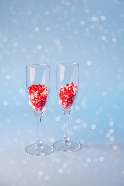 Bicchieri di champagne con caramelle di zucchero a forma di cuore rosso. su sfondo blu. concetto di celebrazione di san valentino, anniversario o matrimonio. copia spazio. Foto Premium