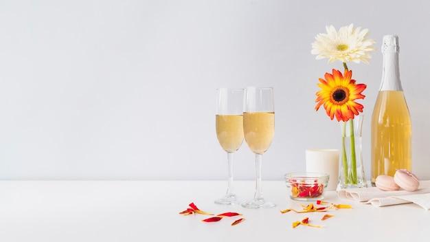 Bicchieri di champagne con fiori sul tavolo Foto Gratuite