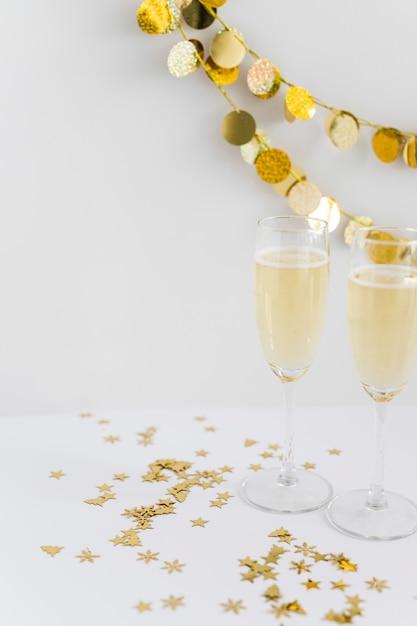 Bicchieri di champagne con lustrini sul tavolo Foto Gratuite