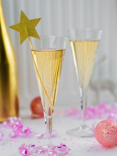 Bicchieri di champagne con nastro rosa e stella Foto Gratuite