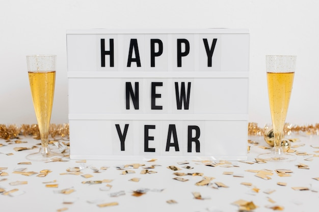 Bicchieri di champagne con segno di felice anno nuovo Foto Gratuite