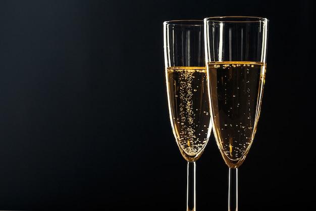 Bicchieri di champagne per occasioni festive contro uno sfondo scuro Foto Premium