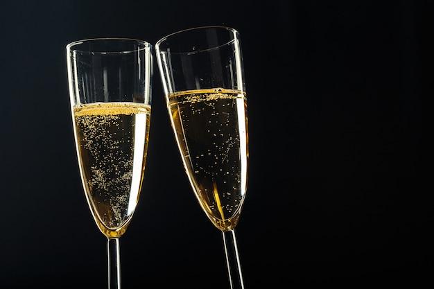 Bicchieri di champagne per occasioni festive su uno sfondo scuro Foto Premium
