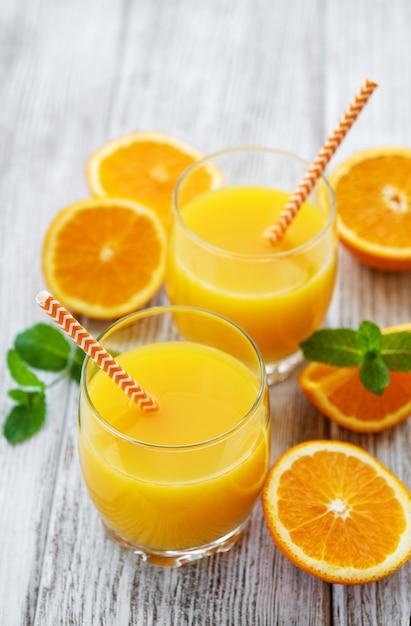 Bicchieri di succo e frutta arancione Foto Premium