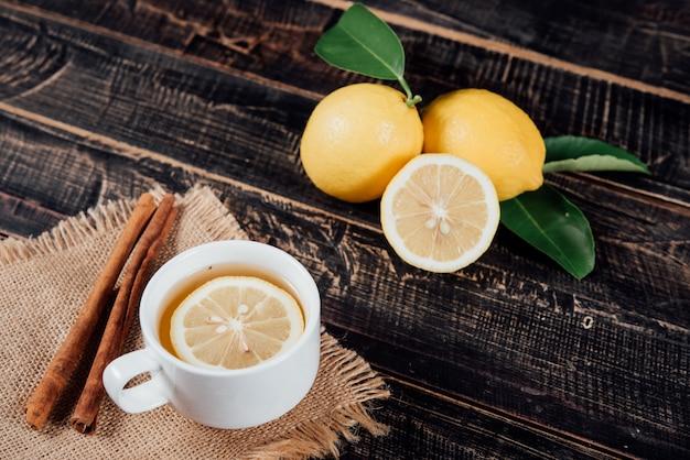 Bicchieri di tè con limone, fette di limoni su un tagliere Foto Gratuite