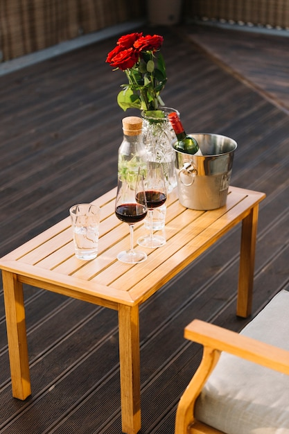 Bicchieri di vino e secchiello per il ghiaccio con la bottiglia di vino sulla tavola di legno al patio Foto Gratuite