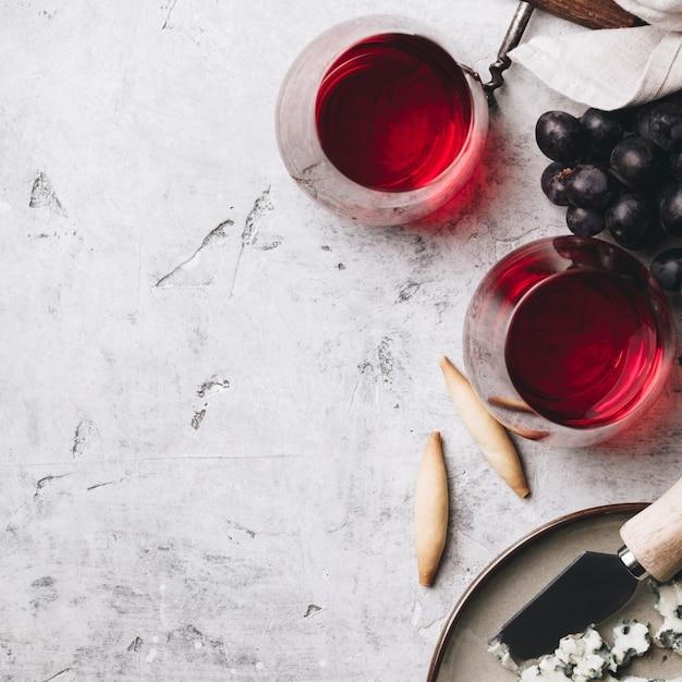 Bicchieri di vino rosso, formaggio e uva sul tavolo di cemento rustico Foto Premium
