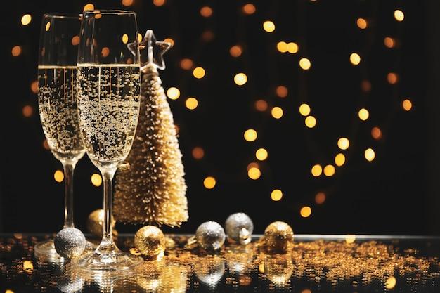 Bicchieri e bagattelle di champagne contro luci sfocate spazio, spazio per il testo Foto Premium
