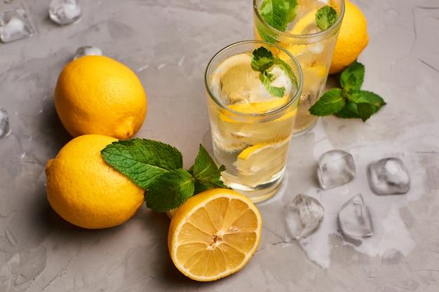 Bicchieri pieni di acqua pura con fettine di limone circondati da alcuni limoni interi, foglie di menta fresca e pezzi di ghiaccio sulla superficie del cemento grigio, sfondo scuro. Foto Premium