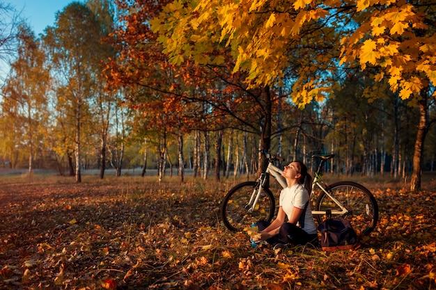 Bicicletta da equitazione nella foresta di autunno, motociclista della giovane donna che si rilassa dopo l'esercizio sulla bici, stile di vita sano Foto Premium