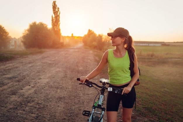 Bicicletta di guida del giovane ciclista felice della donna in periferia. Foto Premium