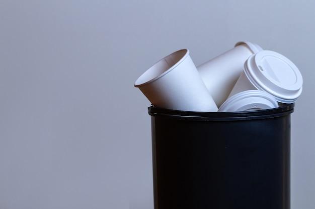 Bidone della spazzatura traboccante di carta, tazze di caffè. dipendenza da caffè e bere molto sfondo di tazze di caffè Foto Premium