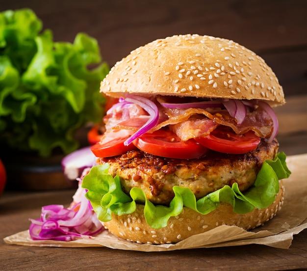 Big sandwich - hamburger con carne di manzo, cipolla rossa, pomodoro e pancetta fritta. Foto Gratuite