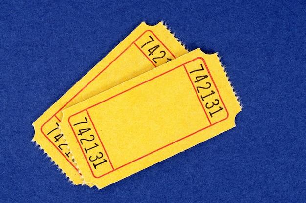 Biglietti di ingresso giallo bianco su uno sfondo di carta blu chiazzato. Foto Premium