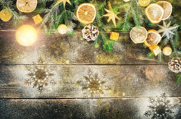 Biglietto di auguri di natale con doni, candele, coni, bastoncini di cannella, arancio secco, albero verde Foto Premium