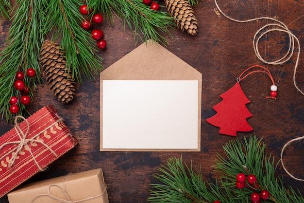 Biglietto di auguri di natale con ramo di abete, regali, confezione regalo e busta. vista dall'alto di sfondo in legno Foto Premium