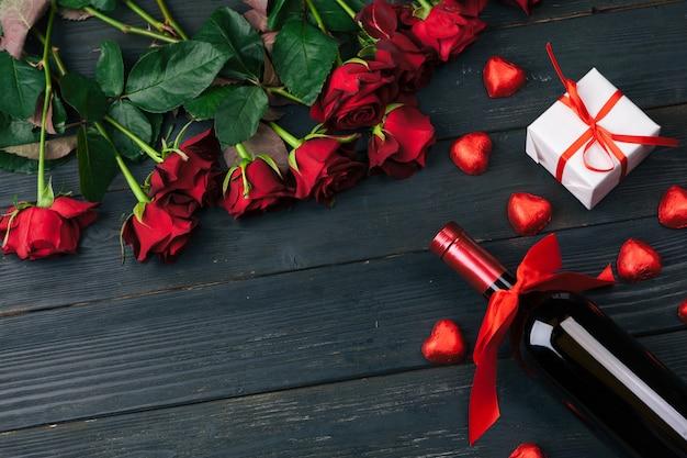 Biglietto di auguri di san valentino. fiori della rosa rossa, vino e contenitore di regalo sulla tavola di legno. Foto Premium