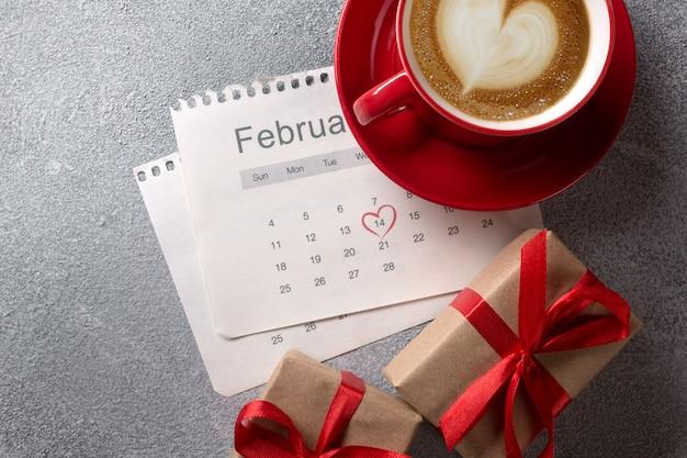 Biglietto di auguri di san valentino. tazza di caffè e contenitore di regalo rossi sopra il calendario di febbraio. vista dall'alto Foto Premium