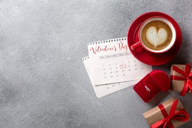 Biglietto di auguri di san valentino. tazza di caffè rosso, anello e confezione regalo oltre il calendario di febbraio. vista dall'alto Foto Premium