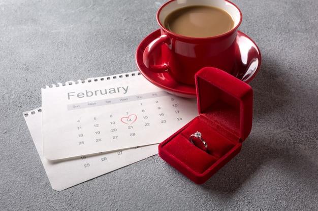 Biglietto di auguri di san valentino. tazza di caffè rosso, anello e confezione regalo oltre il calendario di febbraio. Foto Premium