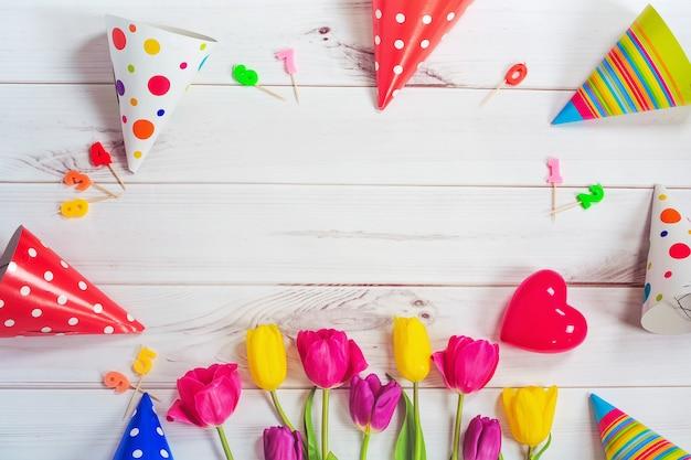 Biglietto di auguri per la ragazza principessa. tulipani, cappello da festa, candela, cuore rosso su legno Foto Premium