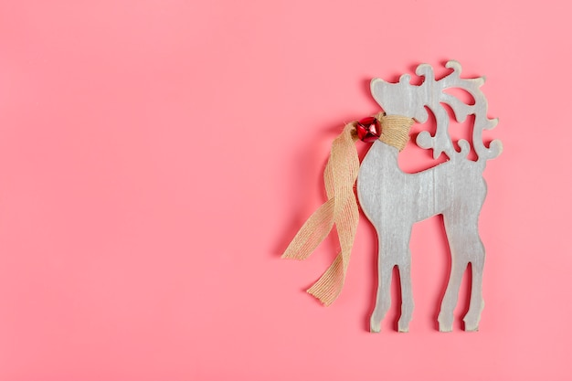Biglietto natalizio. decorazioni di capodanno - cervo in legno con una sciarpa e campana intorno al collo sul rosa Foto Premium