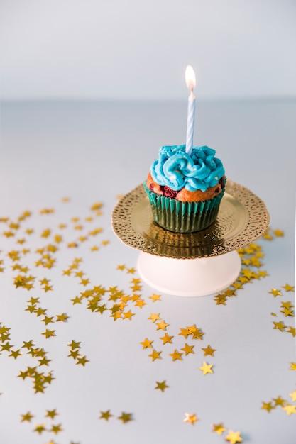 Bigné delizioso di compleanno con la candela accesa sul piatto dorato Foto Gratuite