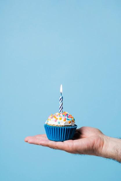 Bigné di compleanno della holding della persona con la candela Foto Gratuite