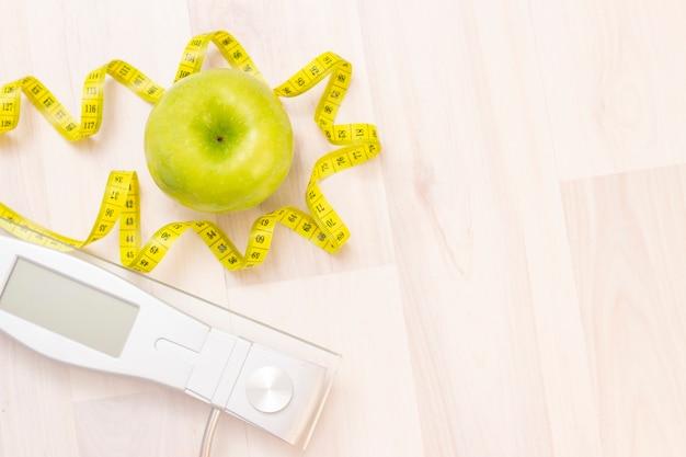 Bilance, mela verde, nastro di misurazione su uno sfondo in legno chiaro. preparazione per la stagione estiva e il concetto di spiaggia, perdita di peso e sport Foto Premium