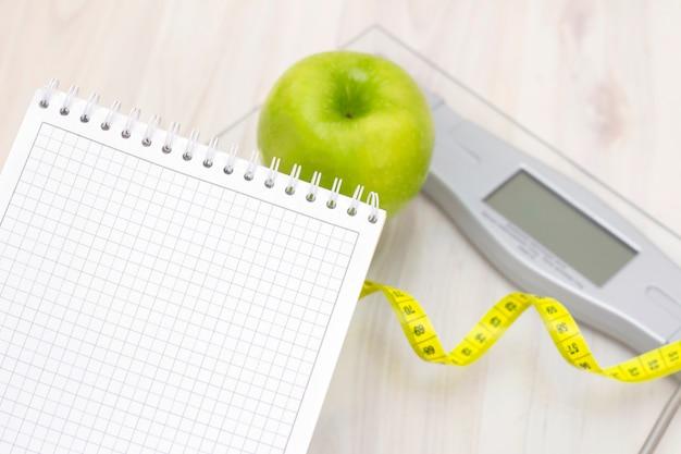 Bilance, una mela verde, un metro e un quaderno per scrivere su una superficie di legno chiaro. preparazione per la stagione estiva e il concetto di spiaggia, perdita di peso e sport Foto Premium