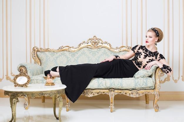 Bionda donna reale su un divano retrò in splendido abito di lusso con un bicchiere di vino in mano. interno. copia spazio Foto Premium