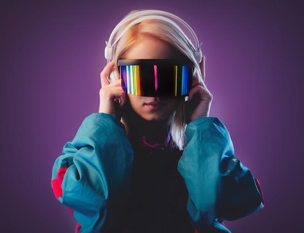 Bionda in occhiali vr e cuffie sulla parete rosa Foto Premium