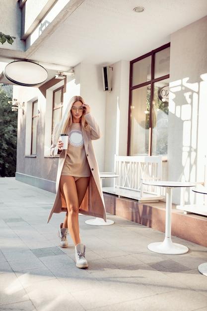 Bionda sexy in lingerie beige e cappotto in posa vicino al caffè. resto e divertimento. Foto Premium