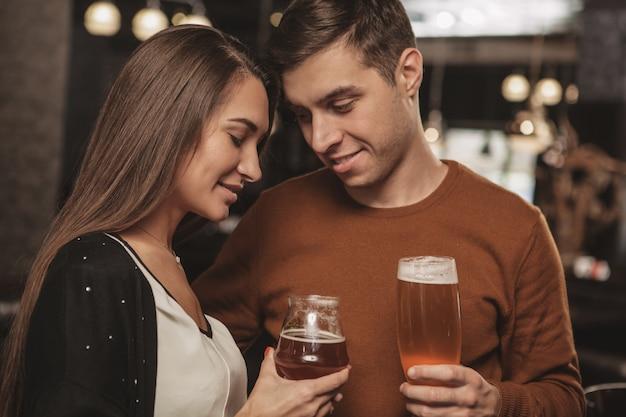 Birra bevente delle giovani coppie felici ad una data al bar Foto Premium