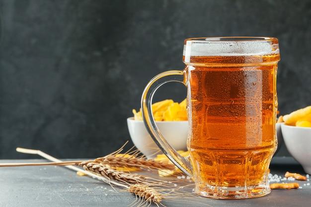 Birra chiara e snack sul tavolo di pietra. cracker, patatine vista laterale Foto Premium